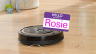 "A Roomba robotic vacuum cleaner cleaning the floor wearing a ""Hello, my name is Rosie"" name-badge."