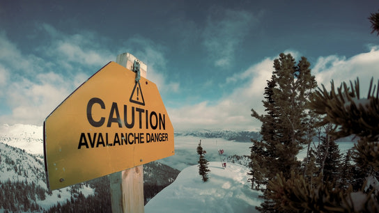 "A warning sign saying ""Caution! Avalanche danger."" with a snow-covered hill in the background."