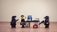 A Lego minifigure set with one scared looking figure sitting at a desk in front of a computer surrounded by two minifigures holding machine guns and wearing tactical armor.