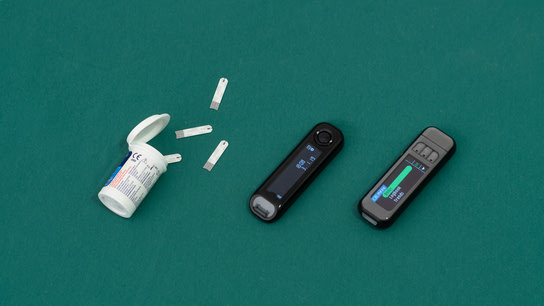 An open box of glucose test strips spills out on a green surface. Two different glucose meters sits next to it.
