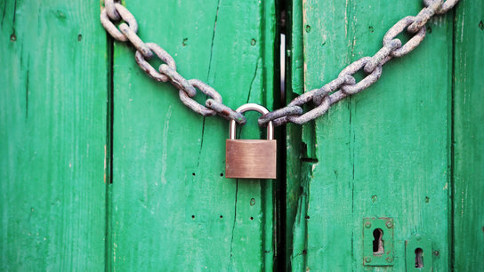 A green door secured by a chain and a padlock.