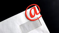 "An envelope with a red ""@"" symbol laying on top of it."