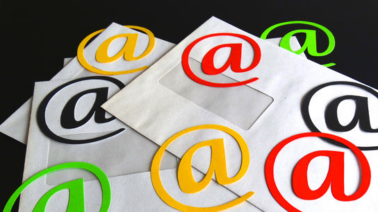 "Envelopes with a cut-out and colored ""@"" symbols laying on top of them."