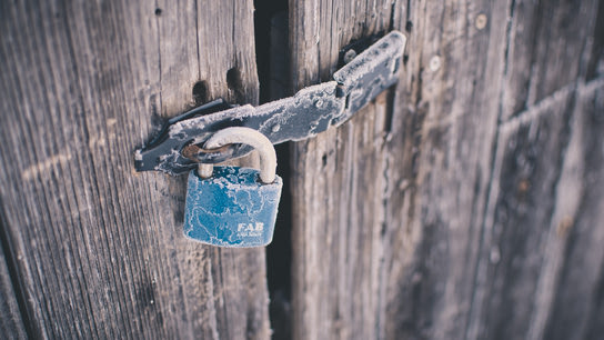 A frosted blue padlock securing an old wooden door.