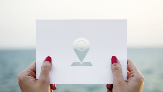 A pair of hands holding up a paper card with a geolocation marker icon cut out of the paper.