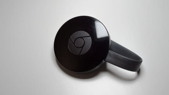A second-generation Google Chromecast device sitting on a table.
