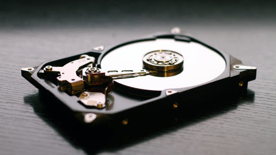 An open hard drive resting on a table exposing the internal disk and read head.