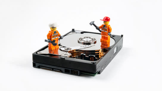 Two construction worker Lego-minifigures standing on top of a hard drive with the internal disk and read head exposed.