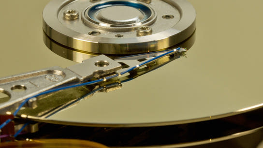An internal close-up of a hard drive disk and its read head.