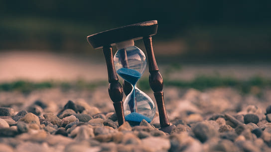 An hourglass with blue sand halfway through its countdown is resting on some rocks.