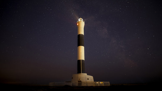 A lighthouse against a stary night sky.