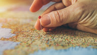 A hand placing a pin on a map.