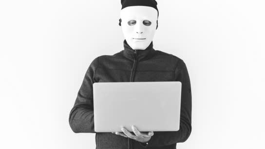A man wearing a black padded jacket and a white mask covering his entire face holds a gray laptop computer.