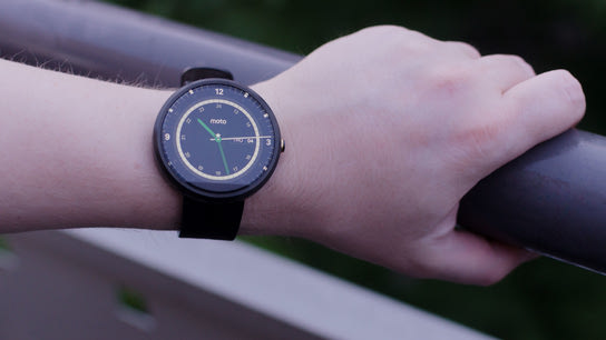 A Moto 360 smartwatch with a lit display worn on a wrist.
