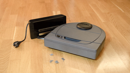 A Neato BotVac D3 robotic vacuum cleaner in front of some dust bunnies with its charging station.