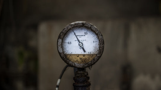 A dirty old mechanical pressure gauge resting at zero.
