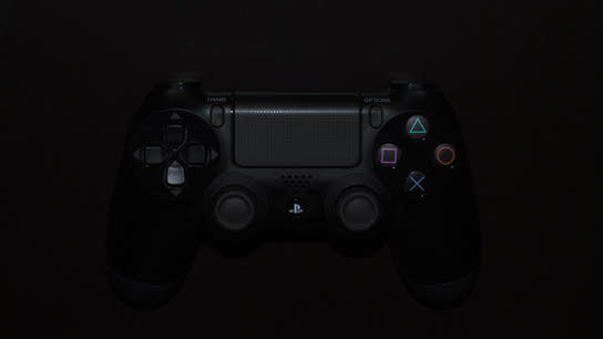 A close-up from above of a PlayStation DualShock 4 controller in the dark.