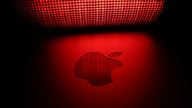 The Apple logo lit up by a red mesh-covered light.