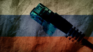 An RJ45 Ethernet connector in front of a worn-out Russian flag.