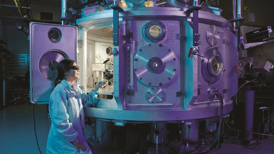 A women scientist wearing a lab coat and protective goggles looking into a big and bulky electronic device.