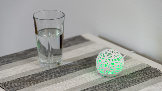 A green glowing Sense sleep monitoring device sitting on a bedside table next to a glass of water.