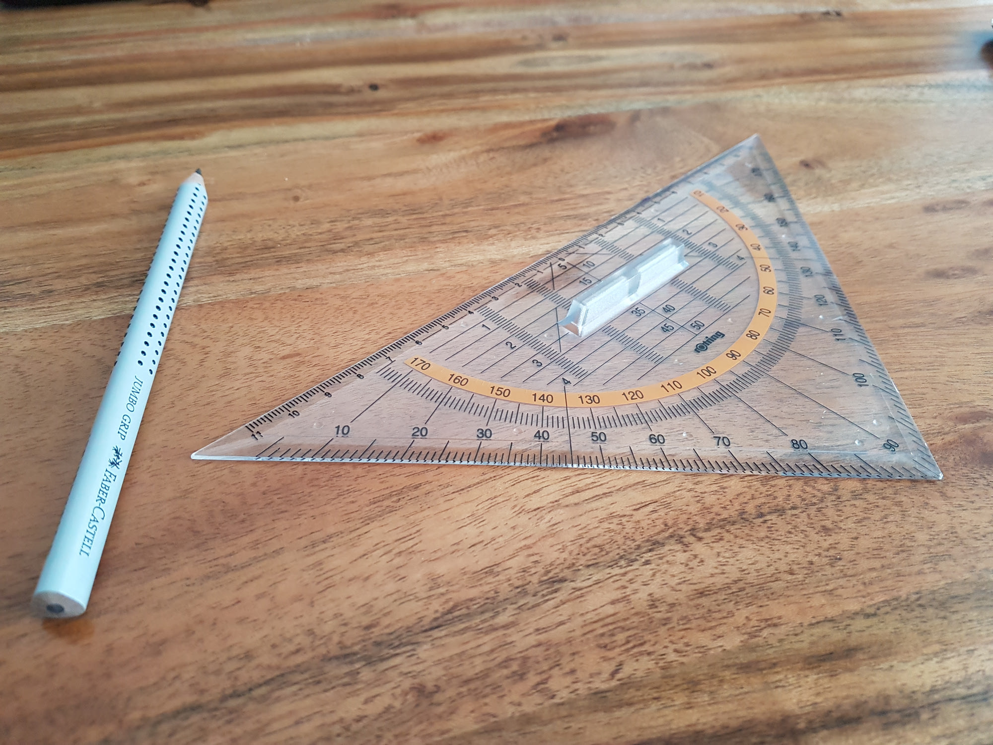A triangular ruler and gray pencil on a wooden surface.
