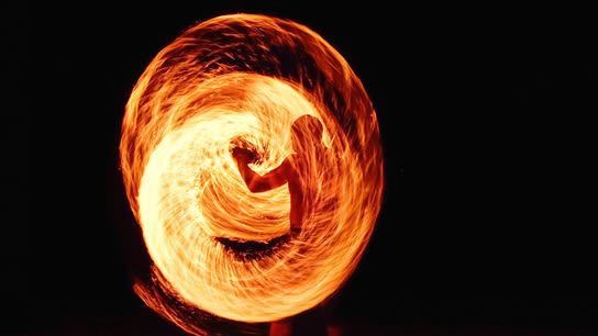 A man swirling a torch in front of him forming a wall of fire.