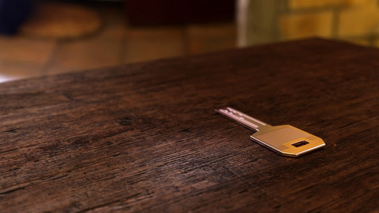 A golden key laying on a table.