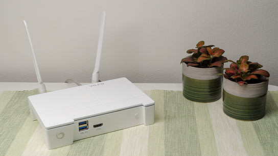 The Vilfo wireless VPN router resting on a table next to two potted plants.