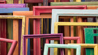 A large stack of worn old window frames in different colors.