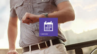 The Outlook Calendar app tile in front with a man checking the time on his wristwatch in the background.