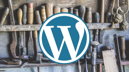 The WordPress logo with a full tool rack in the background.