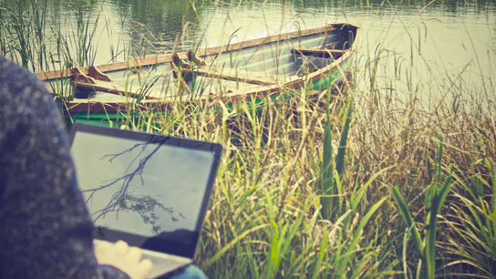 A person working outside on a laptop with a rowboat in the background.